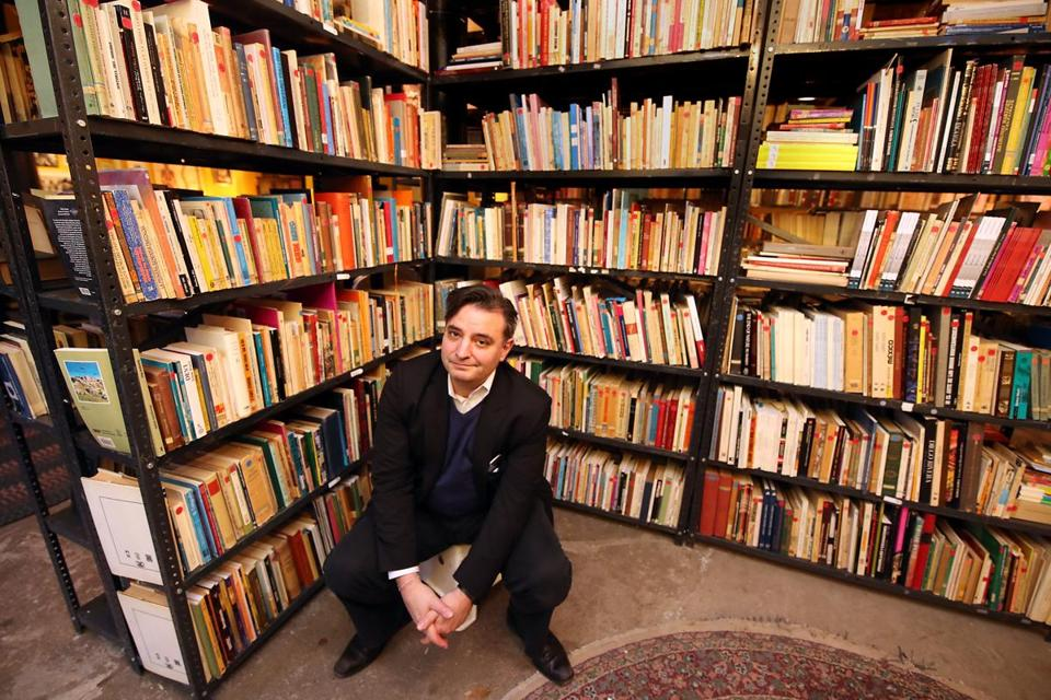 "Pablo Helguera sits in Urbano, an art studio in Jamaica Plain, surrounded by his traveling art project, ""Librería Donceles."""